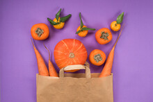 Orange Fruits And Vegetables In Craft Paper Bag On The Violet Background. Pumpkin, Carrots, Persimmon, Tangerines. Beta Carotene Source. Vitamin A.