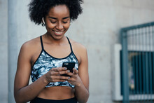 Athletic Woman Using Her Mobile Phone Outdoors.