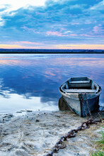 An Old Wooden Boat Is Moored To The Bank With A Rusted Iron Chain On The Bank Of A Calm River Against The Morning Horizon.