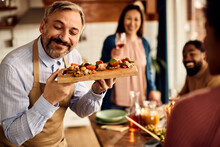 Happy Man Serving Appetizer To His Friends During Lunch Time At Home.