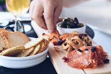 Man's Hand Taking Food From Charcuterie Board With Cured Meats And Dried Fruits