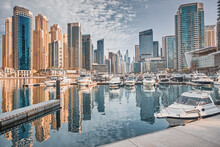 Yacht And Motor Boats Parking At The Port Near Dubai Marina Mall With Row Of High Skyscrapers Residential Buildings And Hotels