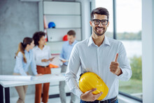 Smiling Male Architect Holding Helmet And Showing Thumbs Up While Standing In Office. There Are His Colleagues Working In Background.