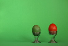 Green And Red Easter Eggs In Modern Decorative Metal Made Eggcups  On Green Background