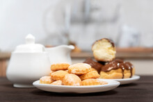 Plate Of Cookies And Eclairs, Sugar Bowl In The Background. Sweet Dessert. Baking For Tea