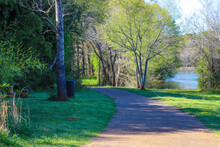 A Concrete Footpath Through The Forest Near A Lake With Lush Green And Autumn Colored Trees Along The Path With Blue Sky At Lake Horton Park In Fayetteville Georgia