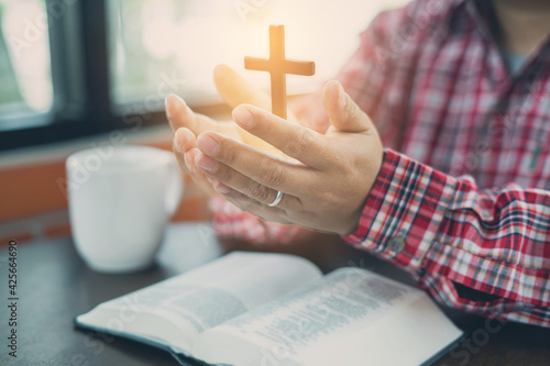Slika na platnu Christian hand while praying and worship for christian religion with blurred of her body background, Casual man praying with her hands together over a closed Bible