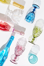 Colored Glasses For Wine And Bottle With Champagne Sparkling On Light With Beautiful Shadows. Summer Party Concept.