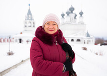 Portrait Of A Happy Smiling Woman In Winter, Standing Against The Background Of The Resurrection Monastery In Murom,..Russia