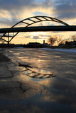 sunset with bridge reflected in puddle on pavement