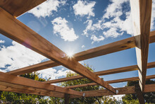 Under Construction Garden Pergola With Wooden Structure In Sunny Backyard Surrounded By Tropical Plants