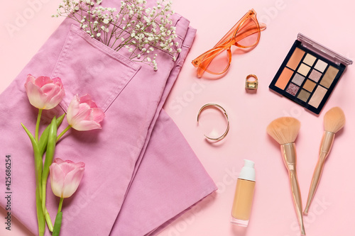 Stylish female accessories with clothes and flowers on color background