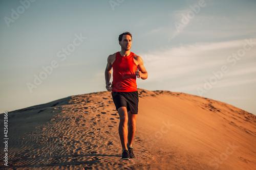 Fototapeta premium Trail runner athlete running man in desert sand dun in heat of summer sunset day.