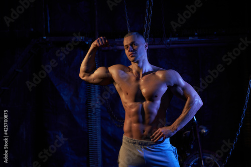 Young shirtless muscular man standing among metal chains, looking at camera, cop Fototapeta