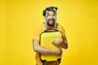 Leinwandbild Motiv male tourist hugs yellow suitcase with hands on isolated background
