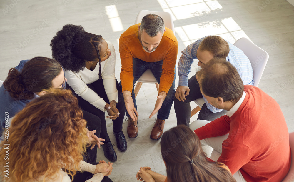 Fototapeta View from above of diverse people talking and supporting each other in group therapy session. High angle shot of multiethnic business team discussing important project in office meeting