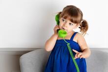 Cute Little Girl Talking On Green Corded Phone