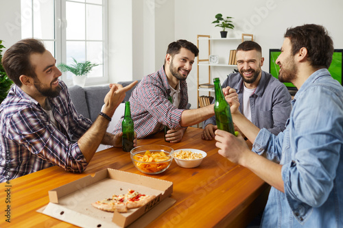 Photo Home gathering and feasting with beer and pizza for male company