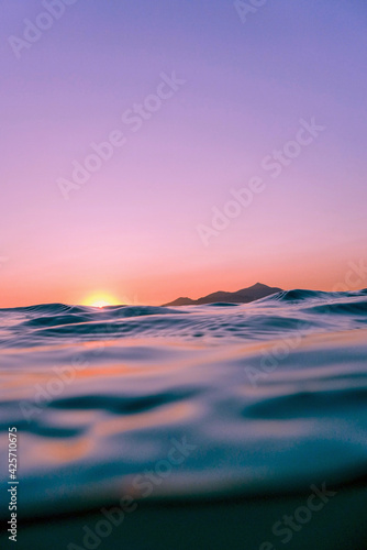 sunset view taken in the water. calming blue waves moving towards the coastline