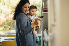 Mother Carrying Baby Texting On Her Cell Phone