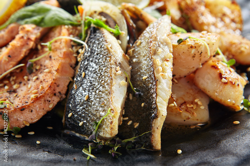 Teppanyaki Style Seafood - Grilled Mixed Seafood with Soy Sauce and Vegetables. Japanese Teppanyaki Salmon Steak, Shrimp, Scallop and Fish Fillet garnished with lemon and green salad.