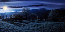 Trees Behind The Fence On The Grassy Meadow At Night. Spring Rural Landscape In Full Moon Light. Distant Mountain Ridge Beneath A Bright Sky With Fluffy Clouds