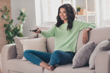 Full Body Photo Of Young Afro Woman Happy Positive Smile Sit Sofa Rest Watch Tv Switch Channel Remote Controller Indoors