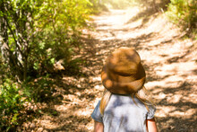 A Little Girl In A Straw Hat Walks Along A Path In The Forest With Sunlight And Shadows From The Trees. View From The Back, The Road Ahead. A Tourist Path In The Fresh Air. Lonely Child Lost, Danger