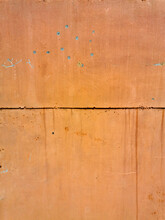 Texture Of Old Painted Rusty Orange Wall Or Garage Door With Peeling And Cracked Paint And Corrosion