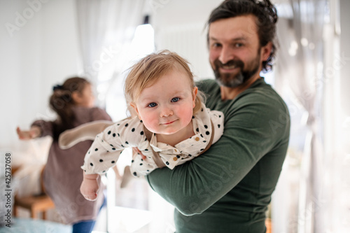 Father with two small daughters having fun indoors at home.