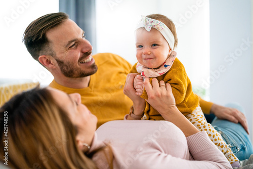 Parents enjoying playing with baby girl at home