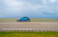 Car On A Dike Defying A Stormy Lake Below A Blue Sky And White Gray Clouds In Spring, Almere, Flevoland, The Netherlands, April 5, 2021