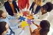 Diverse team connecting puzzle pieces as metaphor for finding solution to problem. High angle shot of happy business people putting together colorful jigsaw parts as symbol of teamwork and cooperation
