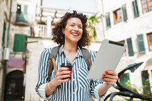 Woman Tourist Walking On The Street In European Old City Using Digital Tablet And Drink Coffee.