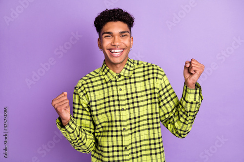 Portrait of attractive cheerful guy wear checked shirt rejoicing good luck isola Fototapeta