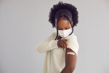 Woman Receives Covid 19 Vaccine Injection. Young Black Lady Showing Arm With Adhesive Plaster Bandage After Getting Vaccinated For Coronavirus. Vaccination Concept, Light Gray Copy Space Background