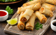 Fried Vegetable Spring Rolls With Sweet Chili And Soya Sauce On Wooden Board