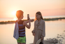 Couple At The Beach At Sunset. Couple Taking Photo Of Themselves