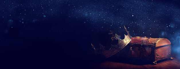 low key image of beautiful queen or king crown over gold treasure chest. vintage filtered. fantasy medieval period