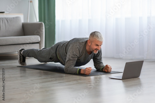 Athletic mature bearded man doing exercises at home, using laptop Wallpaper Mural