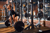 Strong young gentleman working out with weights at gym