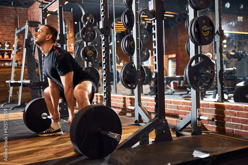 Fototapeta premium Strong young gentleman working out with weights at gym