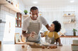 Cheerful smiling Black son enjoying playing with his father while doing bakery at home. Playful African family having fun cooking baking cake or cookies in kitchen together.
