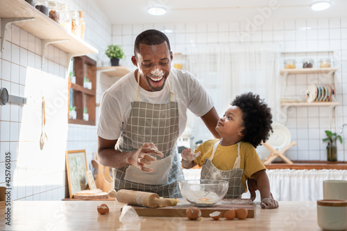 Fotografie, Obraz Cheerful smiling Black son enjoying playing with his father while doing bakery at home