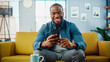 Excited Black African American Man Using Smartphone while Resting on a Sofa in Living Room. Happy Man Smiling at Home and Chatting to Colleagues and Clients Over the Internet. Using Social Networks.