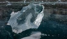 Shiny Transparent Shard Of Ice Close-up. Sharp Edges, Bizarre Shape. Reflection On The Smooth Frozen Surface Of The Lake.