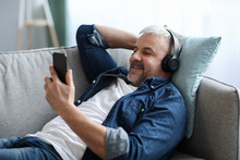 Relaxed Grey-haired Man In Headphones Listening To Music On Smartphone
