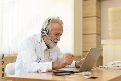 Slika na platnu Senior old doctor wears headset