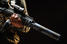 Unrecognizable Special Forces Soldier Standing With Rifle Against Black Dark Background