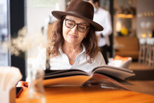 Beautiful Hapy Mature Senior Woman In Glasses And Hat Looking At Menu In Cafe